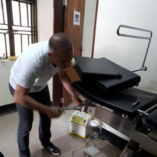 Le Dr Fateri aide à la réparation de la table opératoire