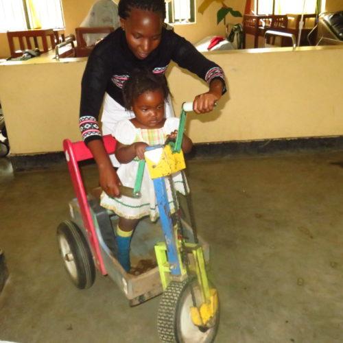 Dianah utilise le  tricycle réparé pour la rééducation